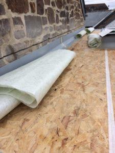 A sheet of fibreglass lies on a flat roof